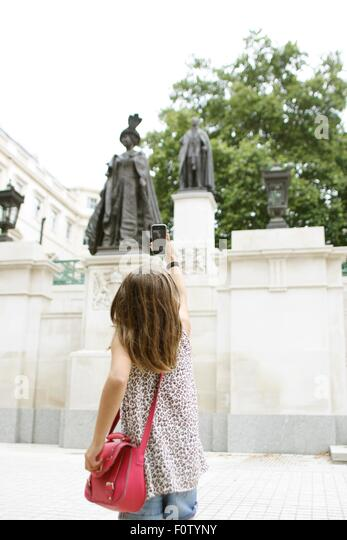 Young girl taking picture of Queen Mother statue with smartphone - Stock-Bilder