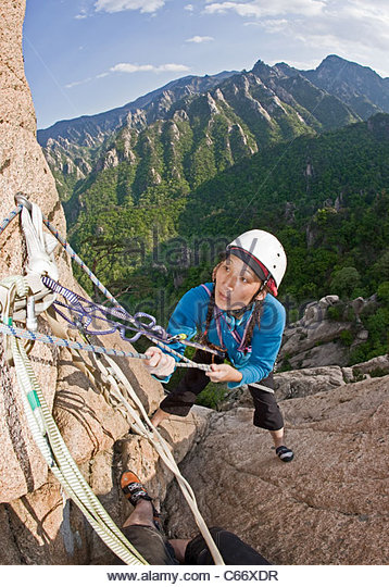 Woman climbing rocky mountainside - Stock Image