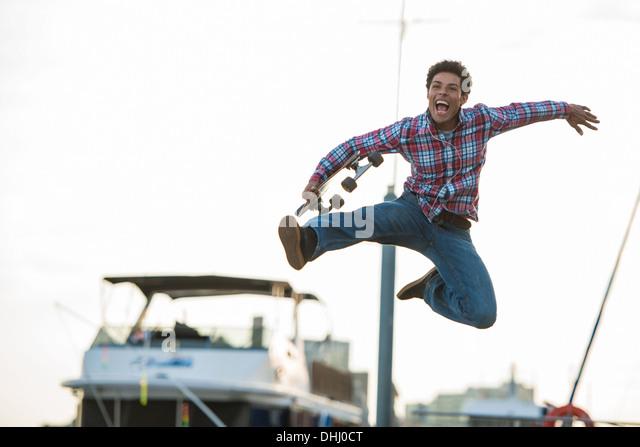 Skateboarder leaping for joy - Stock Image