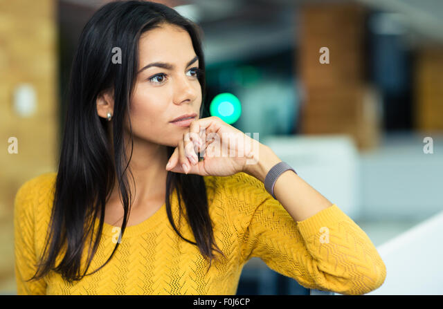Portrait of a pensive businesswoman standing in office - Stock Image