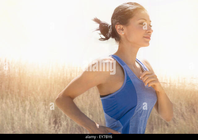 Young woman running outdoors - Stock Image