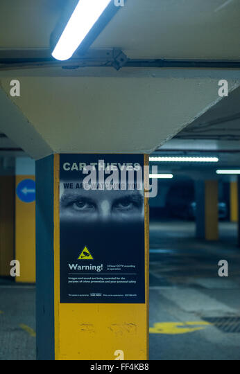 Warning to Car Thieves poster in underground car park, London, UK - Stock Image