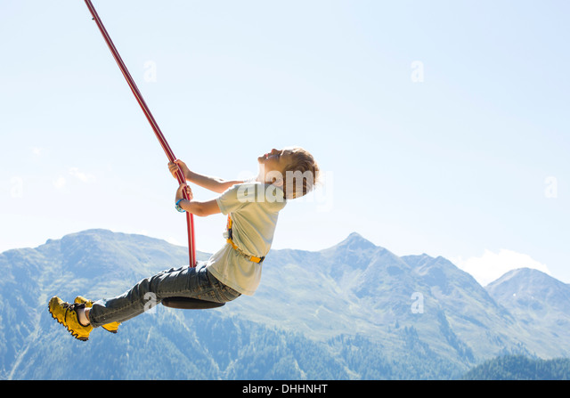 Boy having fun on swing, Tyrol, Austria - Stock Image