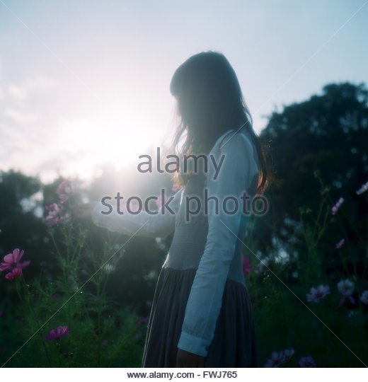 Side View Of A Woman Standing On Landscape - Stock Image