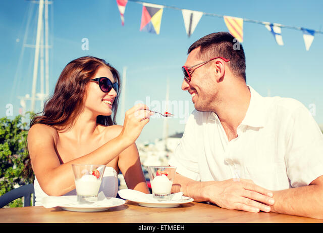smiling couple eating dessert at cafe - Stock Image