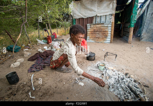 San people, or bushmen cooking food in Botswana, Africa - Stock Image