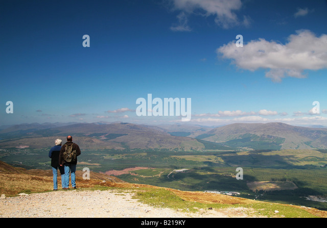two people stood at the top of a mountain admiring the view - Stock Image