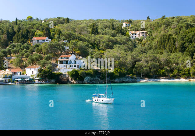 Lakka, Paxos, Ionian Islands, Greece. View from hillside over the clear turquoise waters of Lakka Bay, yacht at - Stock Image