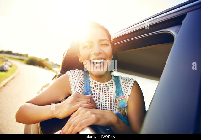 Cute laughing young woman hanging out her head from a car through the open window enjoying the freedom of the breeze - Stock Image