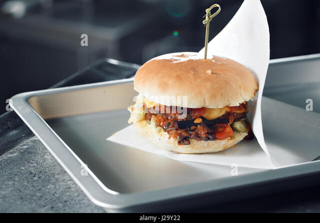 Delicious burgers with beef, tomato, cheese and lettuce. cooked on the grill assembled. - Stock Image