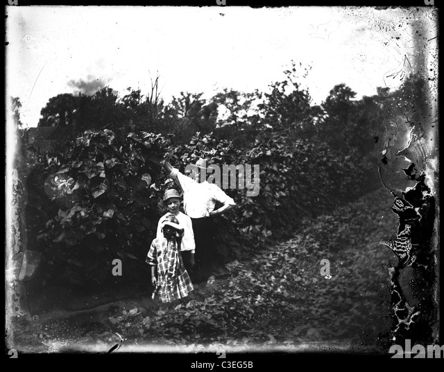gothic family outdoors wooden house 1890s fashion wooden house home homestead man two children - Stock-Bilder