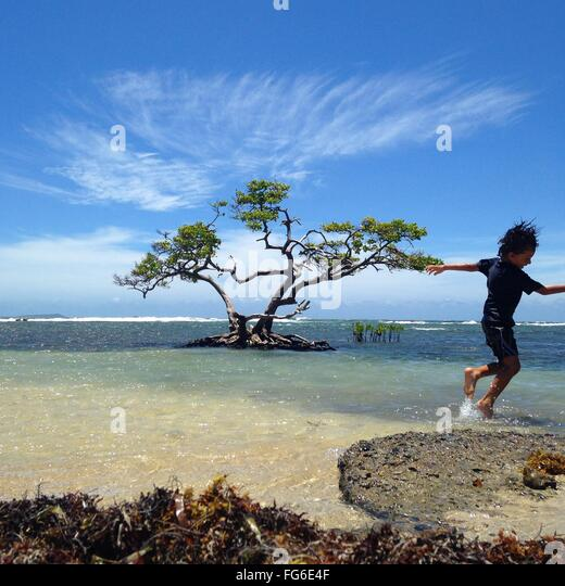 Wet Playful Boy At Beach Against Sky - Stock Image