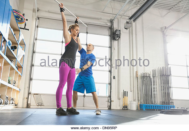 Gym instructor practicing lifting technique with woman - Stock Image