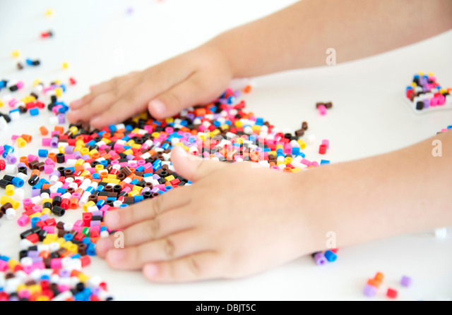 Girl Playing With Ironing Beads - Stock Image