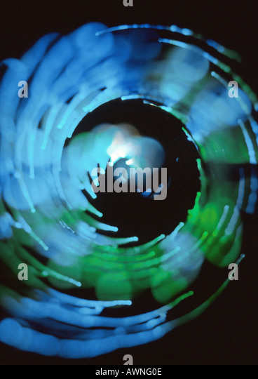 Spiraling light effect, blues and greens, black background - Stock Image