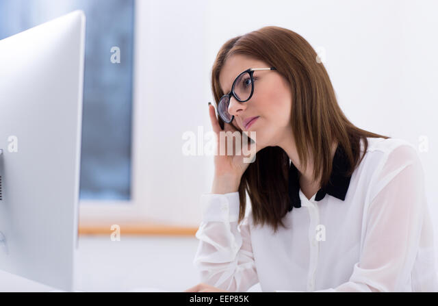 Young businesswoman working on PC at office - Stock Image