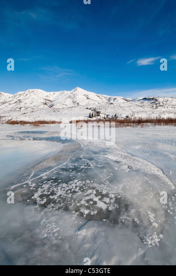 Overflow ice on the North Fork of the Koyukuk River, Brooks Range in the background, Gates of the Arctic National - Stock Image