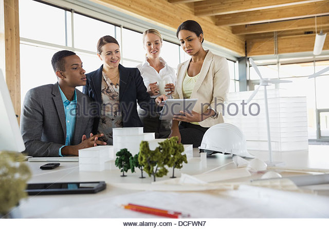 Group of sustainable energy engineers working with digital tablet - Stock Image