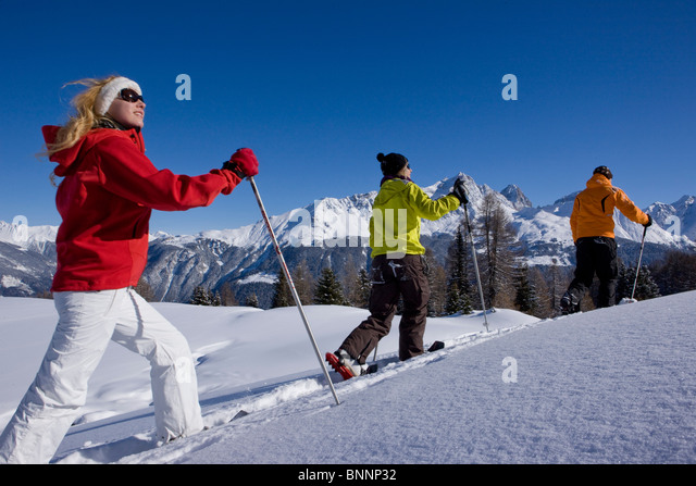 Savognin GR snow shoes snowy shoe running snow group persons tourism winter winter sports canton Graubünden - Stock Image