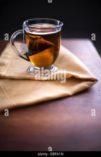A cup of hot black tea on a yellow linen and dark wood surface. Dark morning feel. - Stock Image