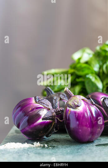 group of aubergines on green marble, with salt foreground and basil in the background. - Stock-Bilder