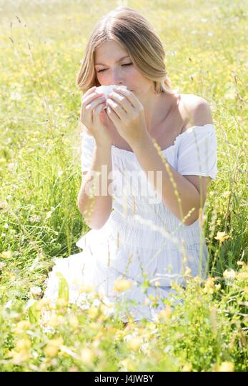 MODEL RELEASED. Young woman blowing nose on tissue. - Stock-Bilder