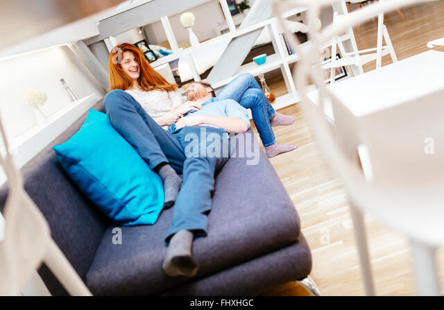 Couple cuddling in beautiful interior living room while lying on sofa - Stock Image