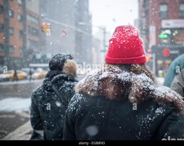 Snow covered pedestrians wait to cross Sixth Avenue in Chelsea in New York on Saturday, February 21, 2015.  A fast - Stock Image
