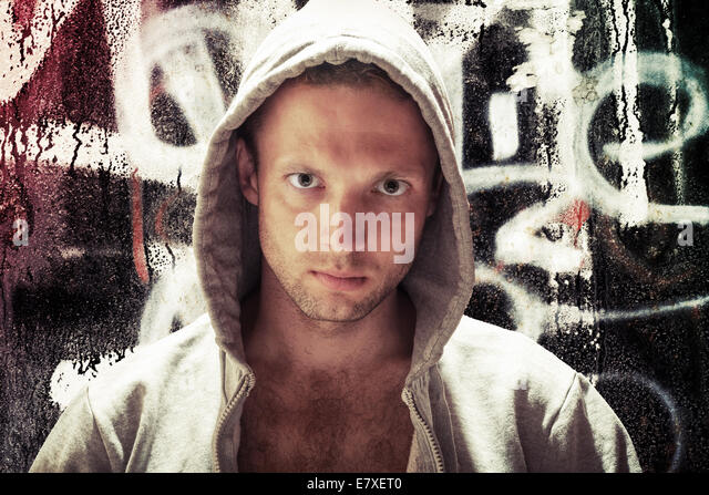 Young Caucasian man in hood, street artist portrait with grungy graffiti wall on background, toned effect - Stock-Bilder