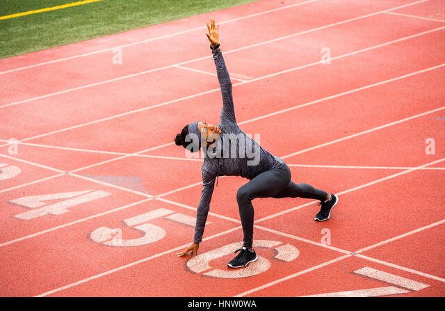 Black woman stretching on track starting line - Stock-Bilder