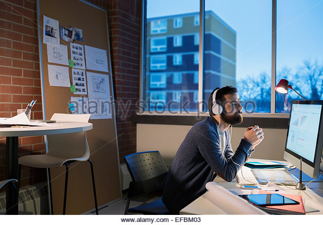 Graphic designer with headphones working late at computer - Stock-Bilder
