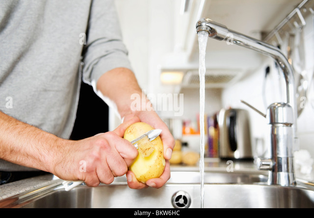 Man peeling potato - Stock Image