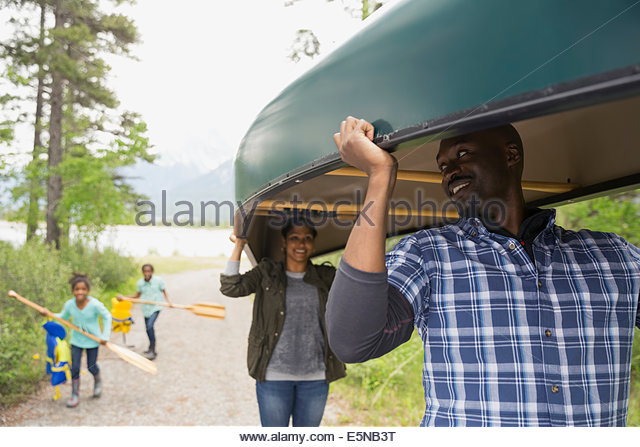 Family carrying canoe and oars - Stock Image