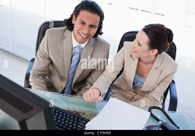 Joyful business team using a computer - Stock Image