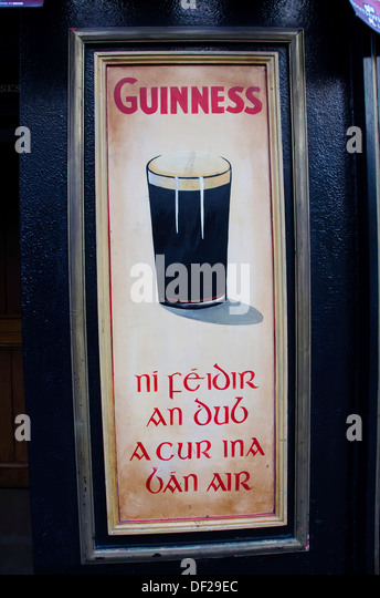 Irish pub with Guinness ad poster in both Gaelic and English, Kilkenny, Ireland - Stock Image