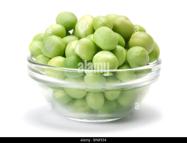 Fresh green peas seed in glass plate on white - Stock Image
