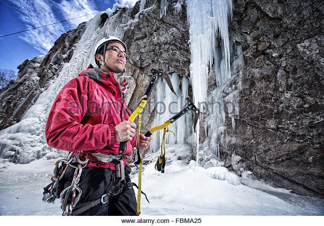 Man preparing to climb frozen waterfall, Lake City, Colorado, America, USA - Stock Image