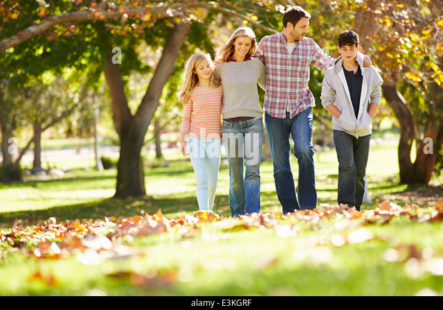 Family Walking Through Autumn Woodland - Stock Image