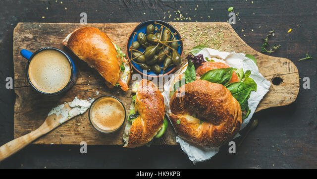 Breakfast with bagel with salmon, avocado, cream-cheese, basil, espresso coffee, capers in blue bowl, rustic wooden - Stock Image