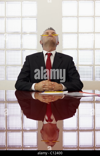 Frustrated mature businessman holding pencil between mouth and nose in office meeting room. Vertical shape, front - Stock Image