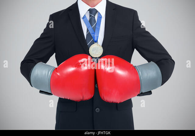 Businessman with boxing gloves against grey background - Stock Image