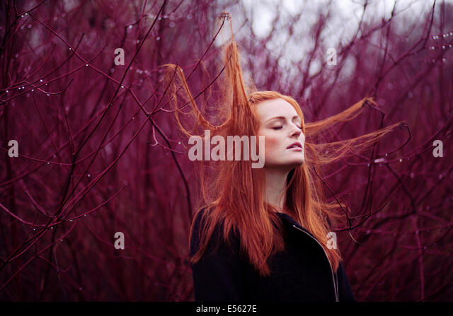 Woman with long red hair between branches, portrait - Stock Image