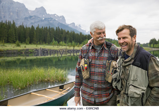 Father and son standing by still lake - Stock Image