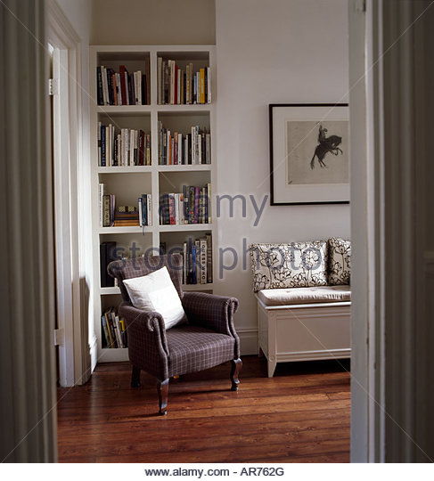 Living room interior with modern stylish bookselves armchair and painting - Stock Image