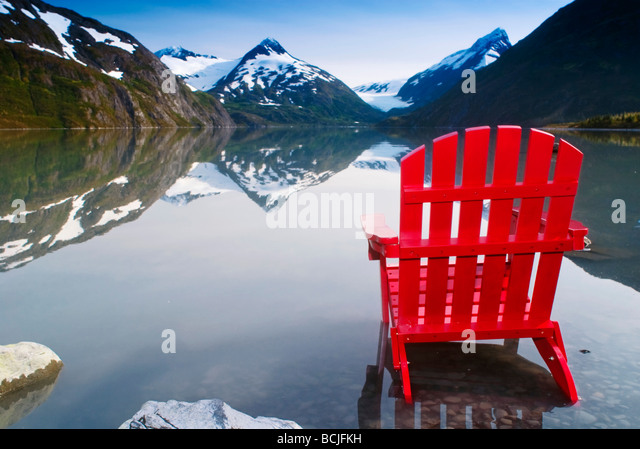 Red Adirondack chair at Portage Lake with Chugach Mountains in the background, Southcentral, Alaska - Stock Image