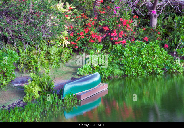 Pond with canoe and garden at Na Aina Kai Botanical Gardens. Kauai, Hawaii - Stock Image