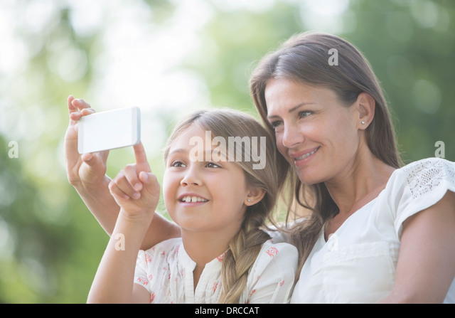 Mother and daughter using cell phone outdoors - Stock Image