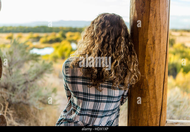 Caucasian woman leaning on wooden porch post - Stock Image