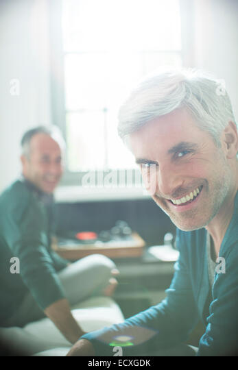 Gay couple relaxing together with record player - Stock Image