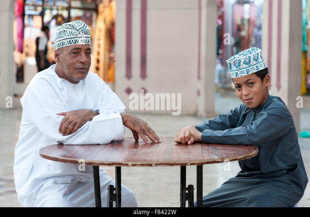 Omani man and his son sitting outside the Mutrah souk in Muscat, the capital of the Sultanate of Oman. - Stock-Bilder